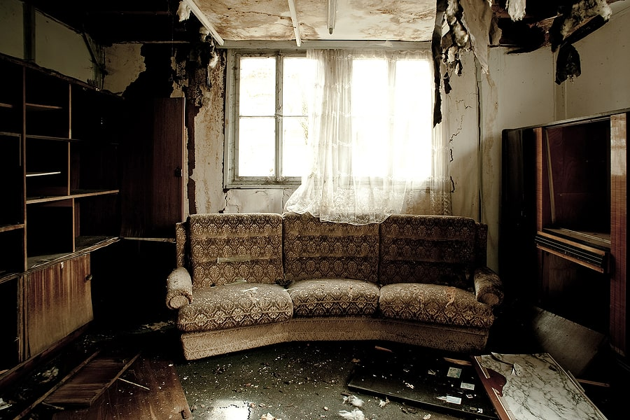 A living room with a couch and burnt walls and curtain