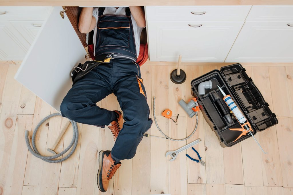 plumber under the kitchen sink