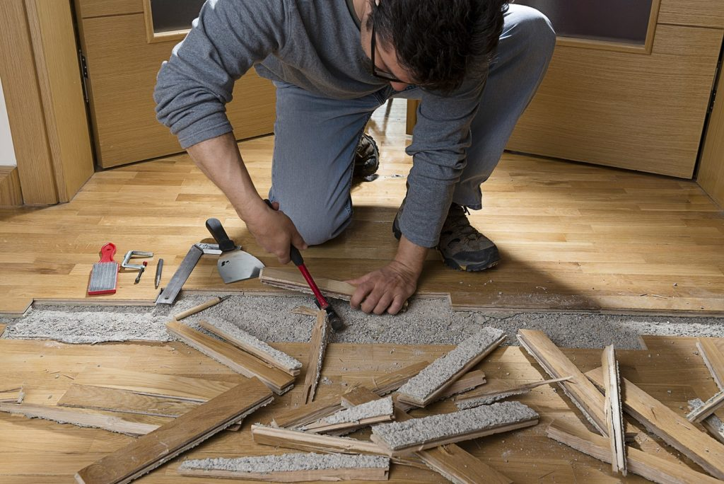 a man repairing hard wood floor