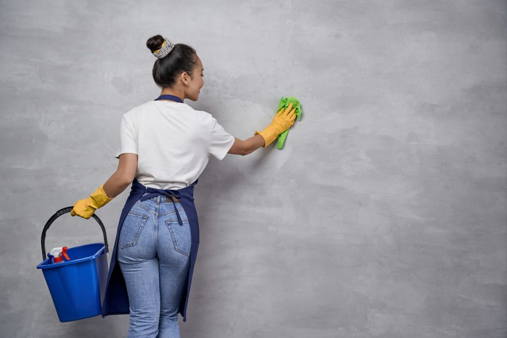young woman uniform holding bucket with cleaning products showing how to clean walls without removing paint